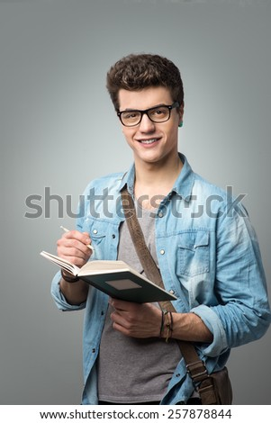 Confident college student reading a book and holding a pencil - stock photo