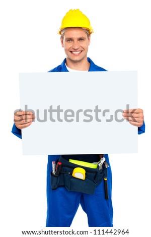 Confident construction worker holding blank billboard isolated over white background