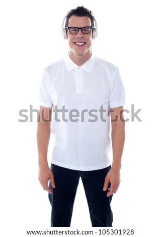 Confident cool guy smiling at front of camera and wearing headphones - stock photo