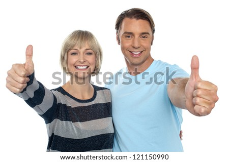 Confident couple showing thumbs up sign to the camera, embracing each other. - stock photo