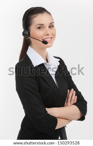 Confident customer service representative. Cheerful young female customer service representative in headset holding her arms crossed and looking at camera while isolated on white - stock photo