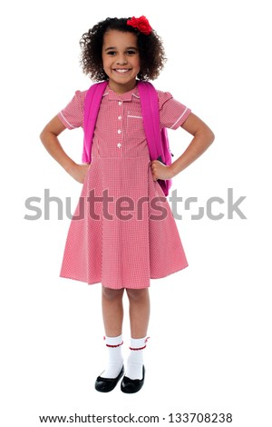 Confident cute school girl in uniform carrying pink backpack with hands on her waist. - stock photo