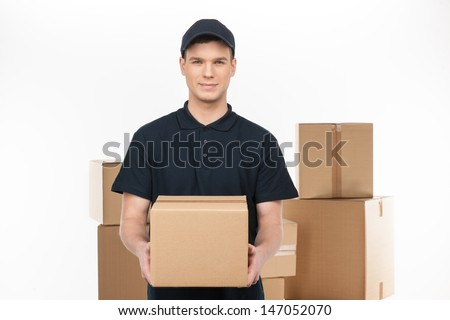 Confident deliveryman.  Cheerful young deliveryman holding a cardboard box while standing in front of the box stack - stock photo