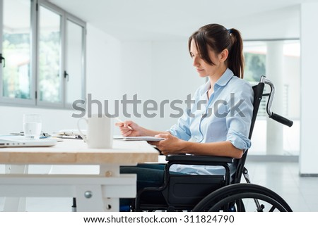 Confident disabled business woman in wheelchair working at office desk and checking paperwork - stock photo