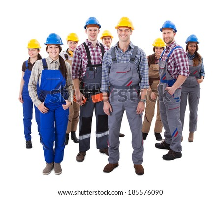 Confident diverse team of workmen and women standing grouped in their dungarees and hardhats smiling at the camera  high angle view isolated on white - stock photo