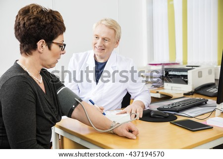 Confident Doctor Checking Female Patient's Blood Pressure