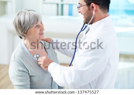 Confident doctor examining his senior patient in hospital