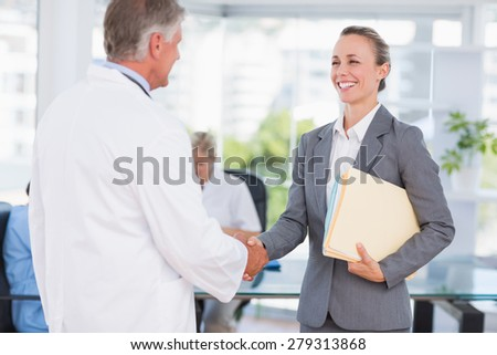Confident doctor greeting pretty businesswoman in medical office - stock photo