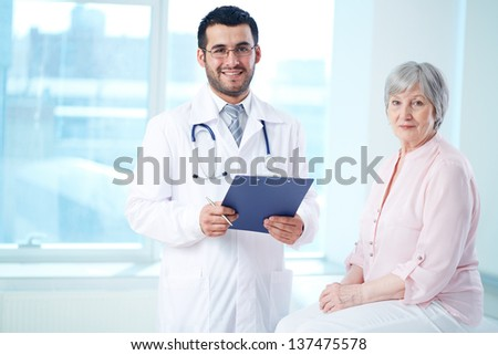 Confident doctor with stethoscope and clipboard and his senior patient looking at camera - stock photo