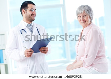 Confident doctor with stethoscope and clipboard looking at his senior patient - stock photo