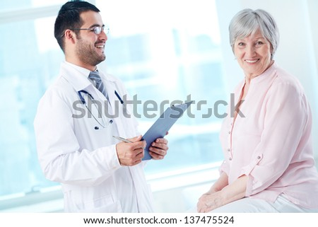 Confident doctor with stethoscope and clipboard speaking to his senior patient while she looking at camera - stock photo