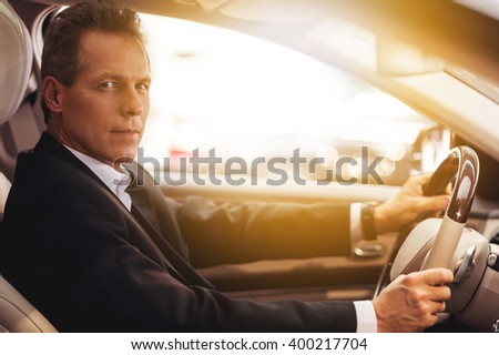 Confident driver. Side view of confident senior man in formalwear sitting in car and looking at camera