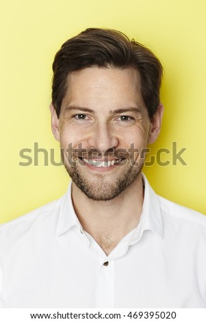Confident dude smiling against yellow background