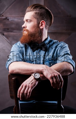 Confident elegance. Profile of a handsome young bearded man looking away and sitting on chair  - stock photo