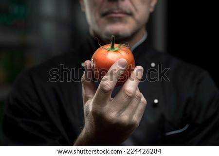 Confident elegant chef holding a delicious tomato on dark background. - stock photo