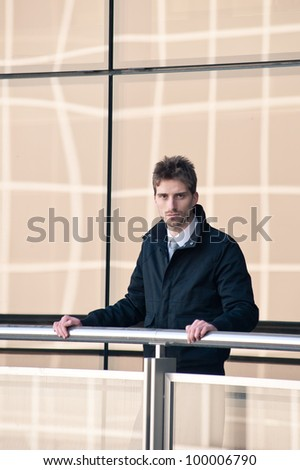 Confident elegant man portrait with windows building background. - stock photo