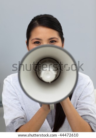 Confident ethnic businesswoman yelling instructions through a megaphone