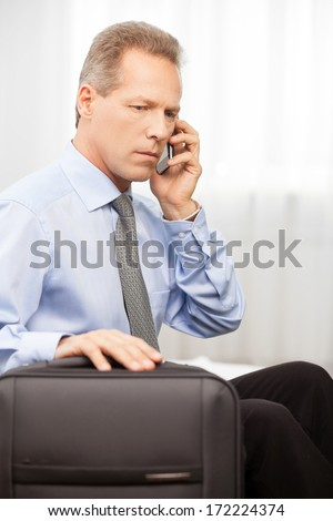 Confident executive. Serious grey hair man in shirt and tie talking on the phone while sitting on bed   - stock photo