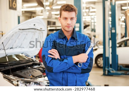Confident expert. Confident young man holding a wrench and looking at camera while standing in workshop with car in the background