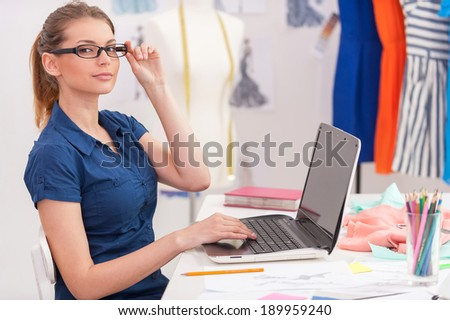 Confident fashion designer at work. Side view of attractive female fashion designer working on laptop and smiling while sitting at her working place - stock photo