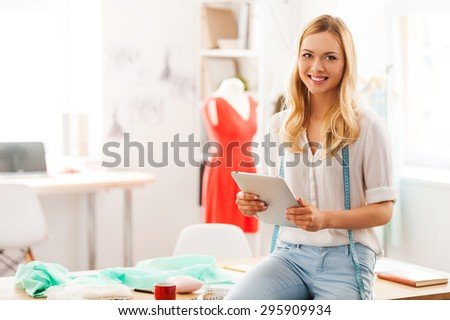 Confident fashion expert. Beautiful young woman holding digital tablet and smiling while sitting on the desk in her fashion workshop  - stock photo