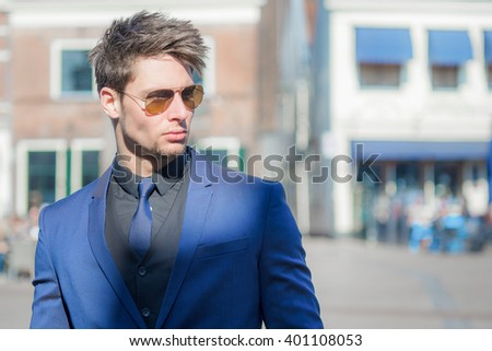 Confident fashionable male model. Sunny and bright street.