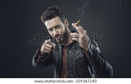 Confident fashionable man in leather jacket smoking a cigar