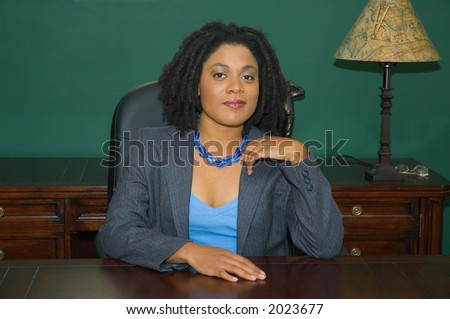 Confident female business executive, sitting behind an impressive desk, in an impressive office.