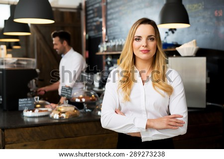 Confident female cafe manager standing at fornt of the bar - stock photo