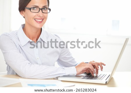 Confident female employee with glasses working on laptop while looking at you - stock photo