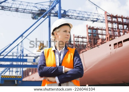 Confident female engineer in shipping yard - stock photo