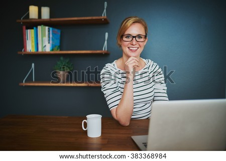 Confident female entrepreneur at office smiling at camera sitting with a laptop - stock photo