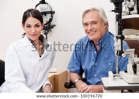 Confident female optometrist smiling with patient in her clinic - stock photo