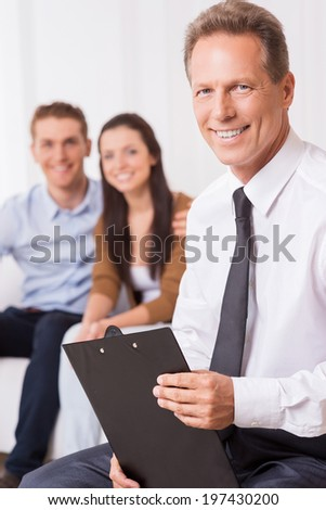 Confident financial expert. Confident mature man in shirt and tie holding clipboard and looking at camera while couple sitting in the background and smiling  - stock photo