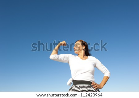 Confident focused and physical strong mature woman showing off her biceps, isolated with blue sky as background and copy space. - stock photo