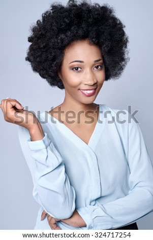 Confident friendly black african businesswoman smiling in studio, isolated on grey background - stock photo