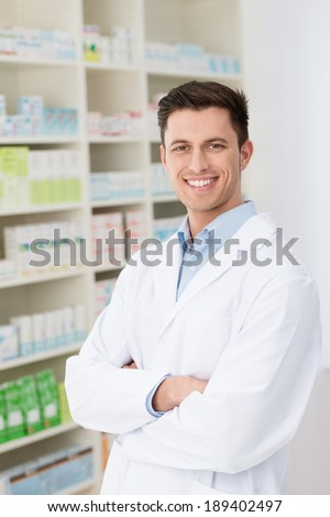 Confident friendly male pharmacist standing with folded arms in his white lab coat in the pharmacy with shelves of stock smiling at the camera
