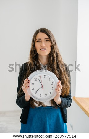 Confident Friendly Young Caucasian  Woman Holding A Large Clock In Hands Showing The Success And Joy Of Good Office Timekeeping In A Happy Hour Concept - stock photo