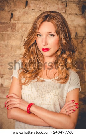 Confident girl standing on a brick wall background. girl with bright red lips - stock photo