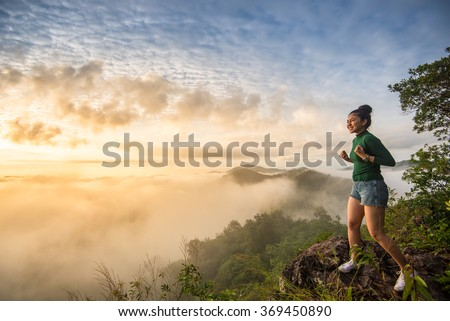 Confident girl standing on top of the mountain before sun rise and say yes.