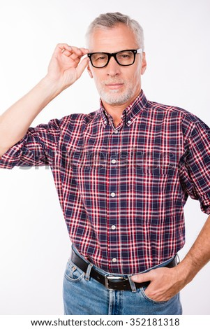 Confident gray aged man with glasses keeping his hands in pockets