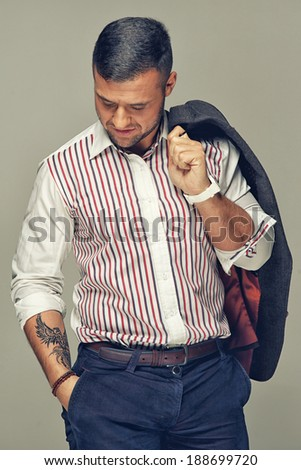 Confident guy with hand in the pocket looking down - stock photo
