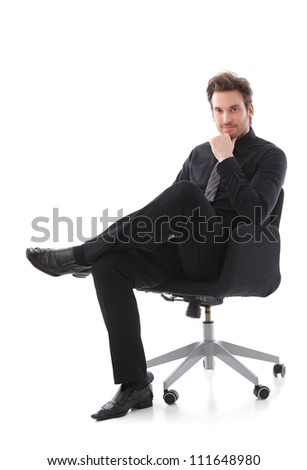 Confident handsome businessman sitting on chair, smiling. - stock photo
