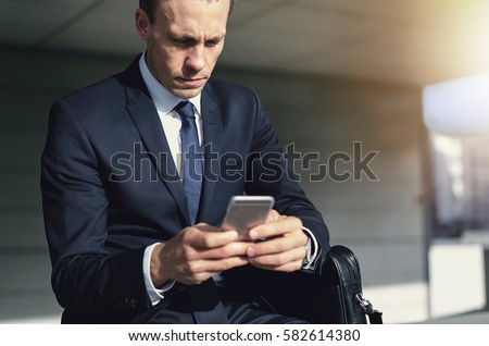 Confident handsome businessman using his phone. Horizontal indoors shot