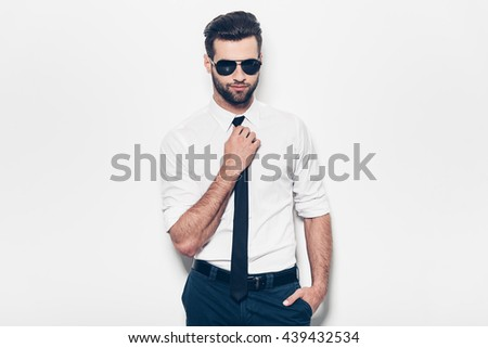 Confident handsome. Handsome young man in white shirt adjusting his necktie and looking at camera while standing against white background  - stock photo