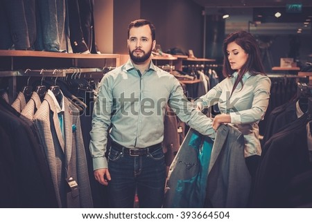 Confident handsome man with beard choosing a jacket in a suit shop. - stock photo