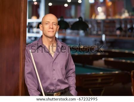 Confident handsome man with pool stick at billiards nightclub - stock photo
