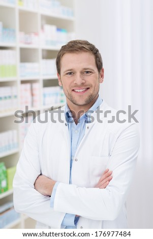 Confident handsome pharmacist with a friendly smile standing with folded arms in the pharmacy - stock photo