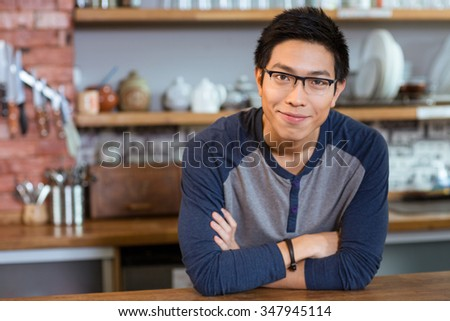 Confident handsome smiling asian young man in glasses standing in cafe with arms crossed - stock photo