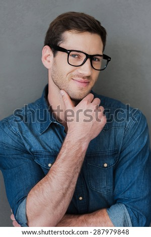 Confident handsome. Smiling young man holding hand on chin and looking at camera while standing against grey background - stock photo